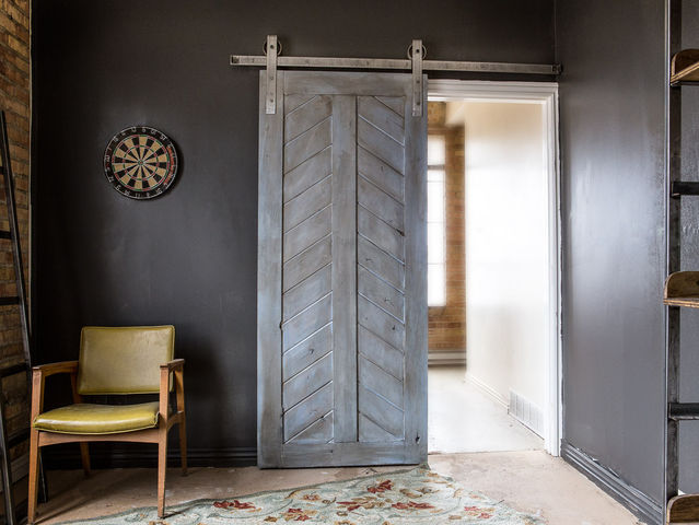 Whether they have one panel or two, barn doors are reclaimed or constructed panels that roll along with the aid of wrought-iron, top-mounted horizontal tracks and rollers in modern rustic design.