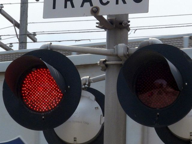 A flashing red light at a railroad crossing means...