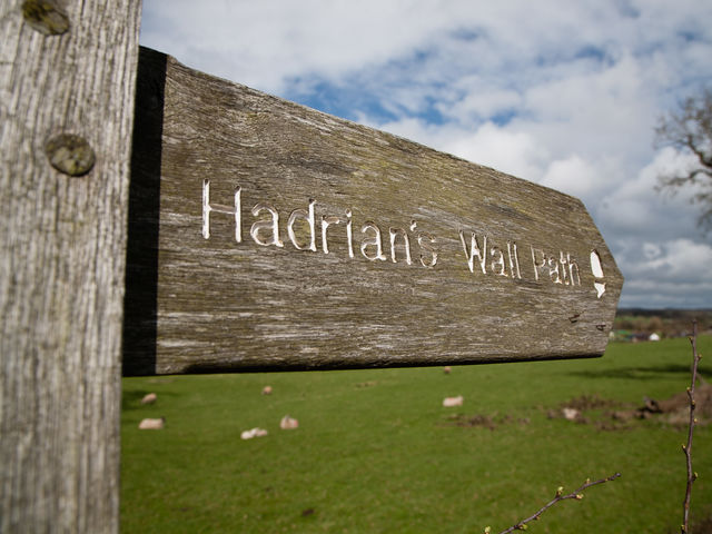 Which road, known locally as the Military Road, runs adjacent to much of Hadrian's Wall?