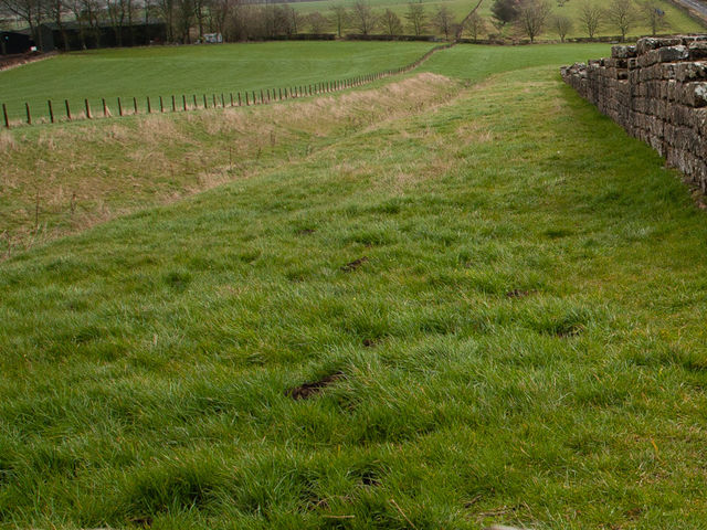 To the North & South of Hadrian's Wall, dug-out and raised structures follow much of the wall. What are these called?