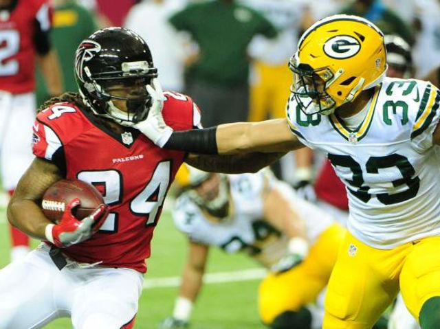 Who were the two quarterbacks the last time the Falcons and Packers clashed in the playoffs?