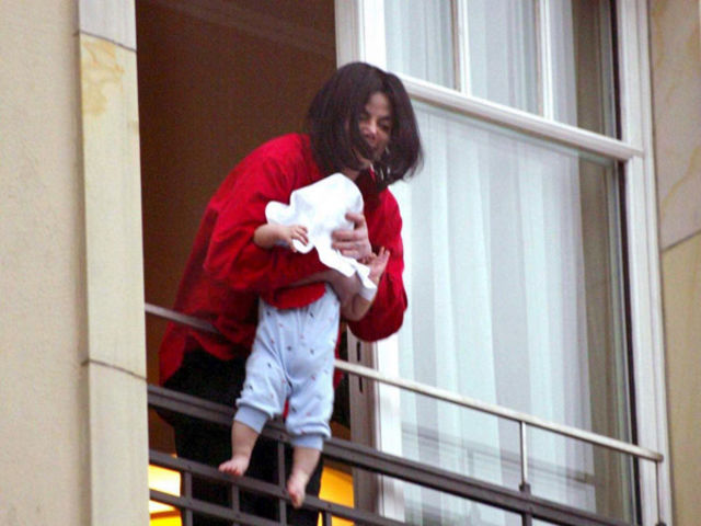 Michael Jackson sparks controversy when he dangles his child over a hotel balcony for photographers.