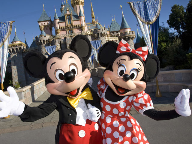 Who has worn more outfits at the parks, Mickey or Minnie Mouse?